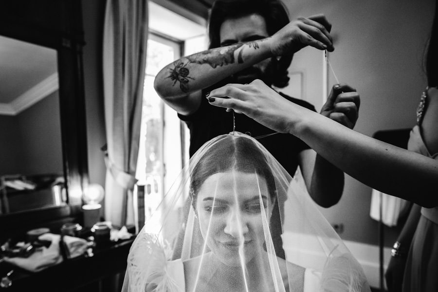wedding photography sewing the veil to the head